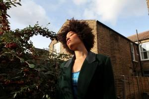 portrait of black artist in her garden taken from a lower perspective