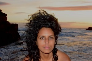 headshot of a disabled, non-binary person of colour against a seascape