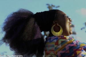 Side profile of a black female singer with a large gold earring and tied up head of hair