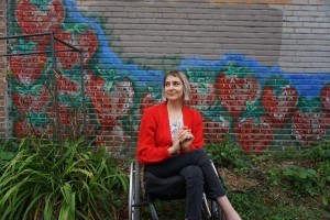 photo of white woman in her wheelchair sitting with a backdrop of a brick wall covered with flower graffiti