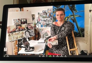 a white female artist with short hair and crutches sits in her studio