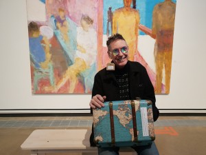 Still from The Disordered Eye showing a white man smiling at the camera with a suitcase with the map of the world on it. A large bright painting of figures is on a gallery wall behind him