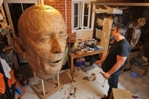 Man standing in a workshop looking at a giant sculpture of a head made of cardboard