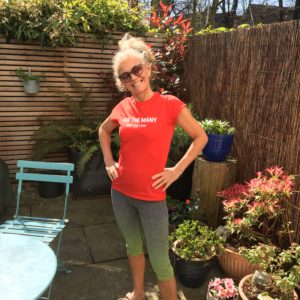 Photo of white woman in a red t-shirt standing in her garden